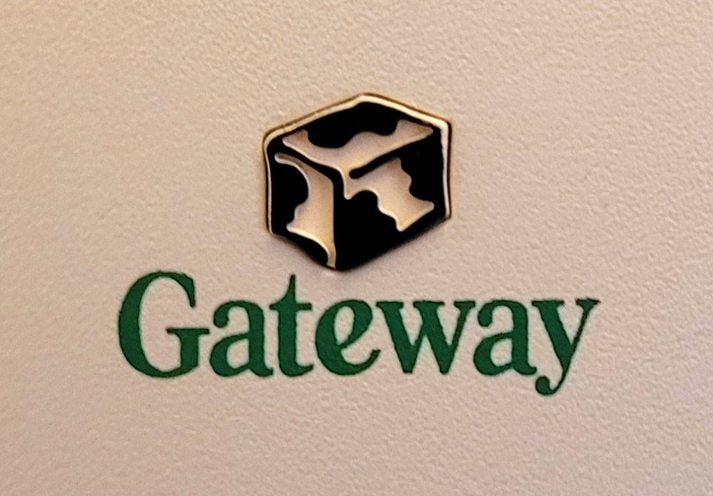 """The 1998 Gateway 2000 logo with the word """"Gateway"""" in green and an abstract cow-print isometric box above it."""